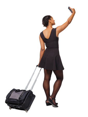 Back view of a black African-American with a suitcase with smartphone. backside view of person.  Rear view people collection. Isolated over white background. A traveler with a suitcase takes a photo by phone.