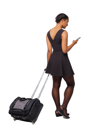 Back view of a black African-American with a suitcase with smartphone. backside view of person.  Rear view people collection. Isolated over white background. Traveler with a suitcase looks into the phone. Imagens