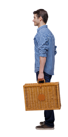 Side view of a man walking with a picnic bag. backside view of person.  Rear view people collection. Isolated over white background. Stylish guy with a wicker suitcase happily looking forward. Imagens