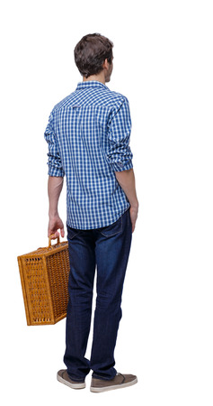 Back view of a man walking with a picnic bag. backside view of person. Rear view people collection. Isolated over white background. A stylish guy with a woven suitcase stands with his hand in his pocket. Imagens