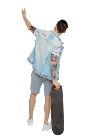 Back view of a pointing man with a skateboard. Rear view people collection.  backside view of person.  Isolated over white background. Guy leaning on a skate shows his hand up.