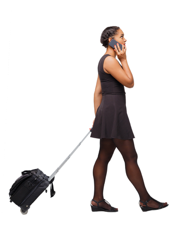 Back view of a black African-American walking with a suitcase. backside view of person.  Rear view people collection. Isolated over white background. The girl at the airport talking on the phone. Imagens