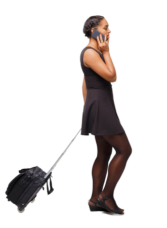 Back view of a black African-American walking with a suitcase. backside view of person.  Rear view people collection. Isolated over white background. The girl at the airport calls a taxi.