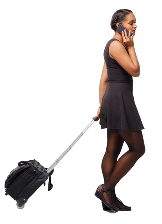 Back view of a black African-American walking with a suitcase. backside view of person.  Rear view people collection. Isolated over white background. The girl rolls a suitcase and calls a taxi.