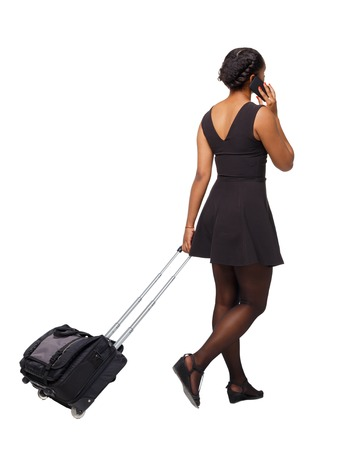 Back view of a black African-American walking with a suitcase. backside view of person.  Rear view people collection. Isolated over white background. Black traveler goes calling a taxi.