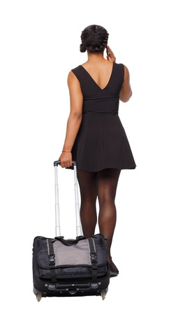 Back view of a black African-American walking with a suitcase. backside view of person. Rear view people collection. Isolated over white background. A black traveler at the airport calls a taxi.