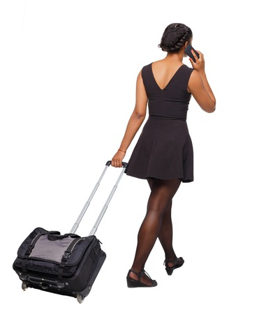 Back view of a black African-American walking with a suitcase. backside view of person.  Rear view people collection. Isolated over white background. Black girl calls a taxi on the go. Imagens