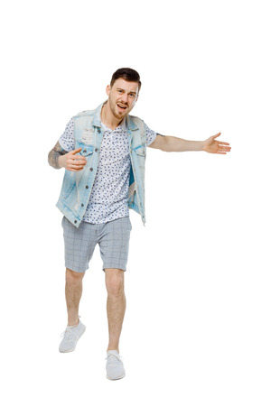 The man screams. Aggressive guy in tattoos yelling at the frame and showing his hands back. An angry guy scandals and understands the problems. Isolated on white background. The guy in the denim vest yells showing back. Imagens