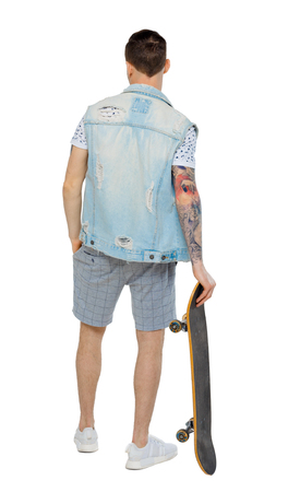 Back view of a man in shorts with a skateboard. A guy posing with a board for skating. Rear view people collection. backside view of person. Isolated over white background. Guy leaning on a skate put his hand in his pocket shorts. Imagens
