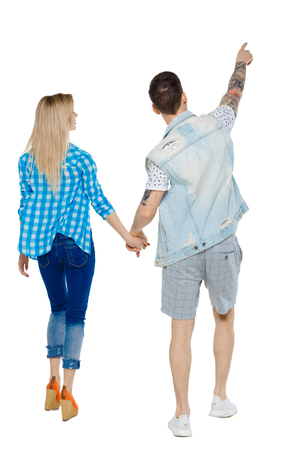 Back view of the couple walking and pointing upwards. Rear view people collection. backside view of person. Isolated over white background. The guy on the go shows the girl sights.
