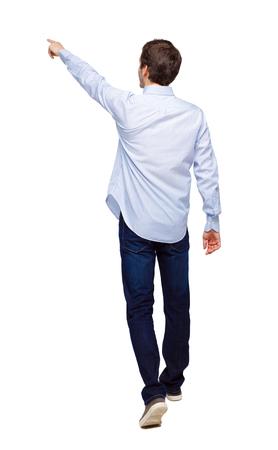Rückansicht eines Mannes, der mit einer zeigenden Hand geht. gehender Kerl zeigt. Rückansicht der Person. Rückansicht-Menschensammlung. Getrennt über weißem Hintergrund. Der Typ im weißen Hemd geht nach vorne und zeigt seine Finger. Standard-Bild