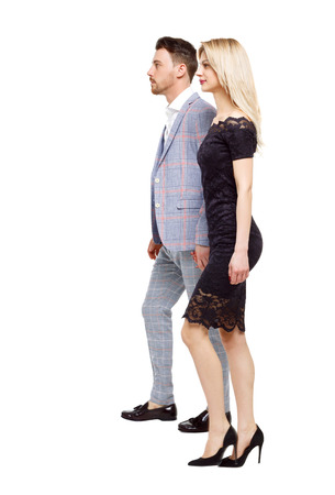 Side view of two walking business people.  Rear view people collection. backside view of person. Isolated over white background. A couple in evening wear holding hands pass by looking ahead of them. 写真素材