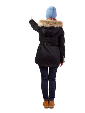Back view of  woman  in parka thumbs up. Rear view people collection. backside view of person. Isolated over white background. A girl in a warm park with fur and a hat shows a sign of success.