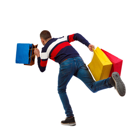Side view of a man in a sweater with shopping bags that runs. backside view of person.  Rear view people collection. Isolated over white background. The guy in the striped sweater runs waving shopping bags.