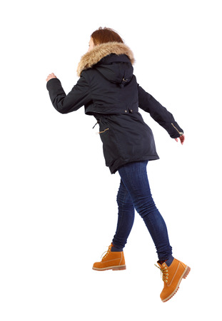 back view of running  woman in winter jacket. beautiful brunette girl in motion. backside view of person.  Rear view people collection. Isolated over white background. Girl warm park with fur runs wide jumps.