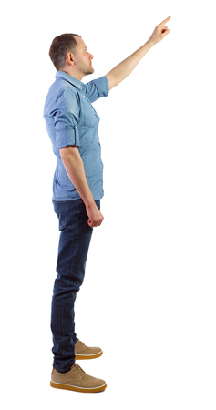 Side view of a man in jeans points his hand upwards. Rear view people collection.  backside view of person.  Isolated over white background. The guy in the blue shirt shows up.