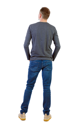 Back view of a stylish man. Rear view people collection.  backside view of person.  Isolated over white background. A young guy in a gray jacket stands with his hands in his pockets and looks up.