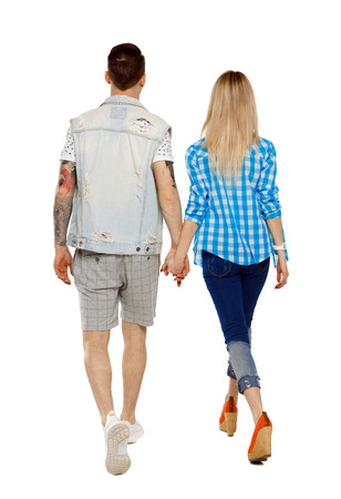 Back view of going couple. walking friendly girl and guy holding hands. Rear view people collection. backside view of person. Isolated over white background. The guy and the girl go hand in hand.