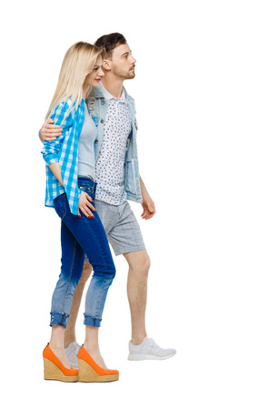 Side view of going couple. walking friendly girl and guy holding hands. Rear view people collection. backside view of person. Isolated over white background. The guy is a girl hugging her shoulders.