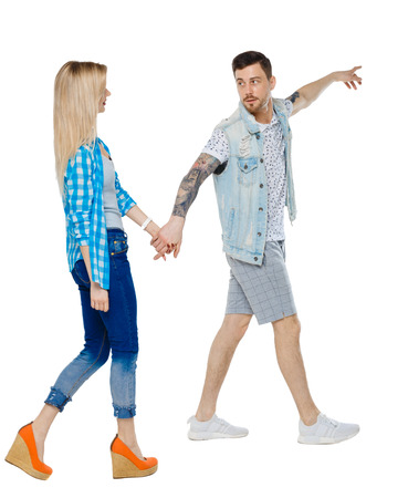 Side view of the couple walking and pointing upwards. Rear view people collection. backside view of person. Isolated over white background. A couple leads by the hand girl showing her sights. Imagens