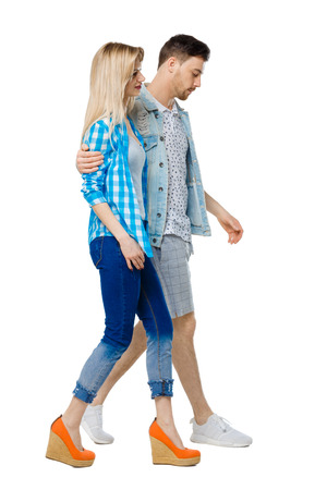 Side view of going couple. walking friendly girl and guy holding hands. Rear view people collection. backside view of person. Isolated over white background. The guy and the girl go embracing.