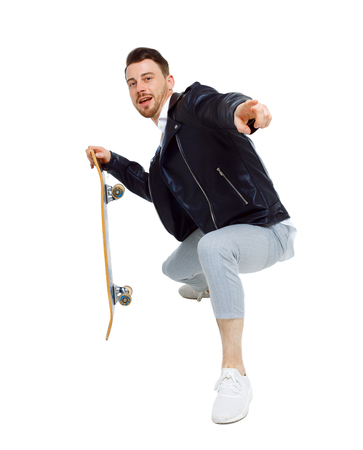 A man with a skateboard. A guy in stylish clothes and trousers posing with a board for skating. Front view. Isolated on white background. Collection of sports people. Stylish guy with a skate.