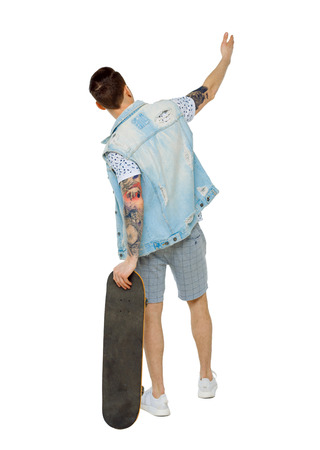 Back view of a pointing man with a skateboard. Rear view people collection.  backside view of person.  Isolated over white background. Tattooed skater shows by hand.