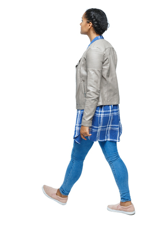 back view of a young black girl walking in jeans and a checkered shirt. beautiful girl in motion. backside view of person.  Rear view people collection. Isolated over white. African American in autumn clothes walking down the street.