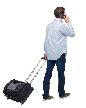 Back view of walking business man with suitcase talking on the phone. Standing young girl. Rear view people collection.  backside view of person. Isolated over white background. Young businessman is rolling a suitcase talking on the phone.
