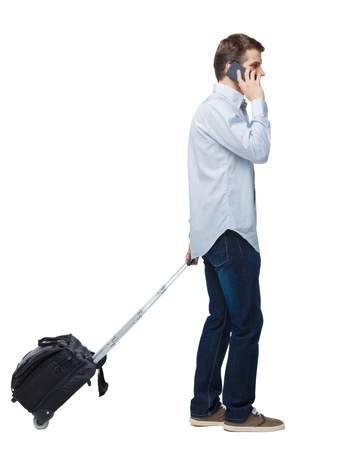 Side view of walking business man with suitcase talking on the phone. Standing young girl. Rear view people collection.  backside view of person. Isolated over white background. A young businessman at the airport calls a taxi. Imagens
