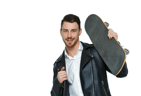 A man with a skateboard. A guy in stylish clothes and trousers posing with a board for skating. Front view. Isolated on white background. Collection of sports people. Stylish guy in a leather jacket posing with a skate on his shoulder. Imagens
