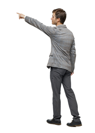 Back view of walking pointing business man. gesticulating young guy in suit. Rear view people collection.  backside view of person.  Isolated over white background. Imagens
