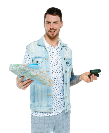 man with a map. Front view. The tourist in the denim jacket is angry or surprised. Isolated on white background. Imagens