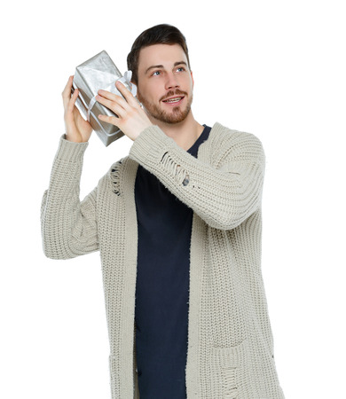 Front view of a man with a gift box. Front view people collection. Isolated over white background. Stylish bearded guy trying to guess a gift.