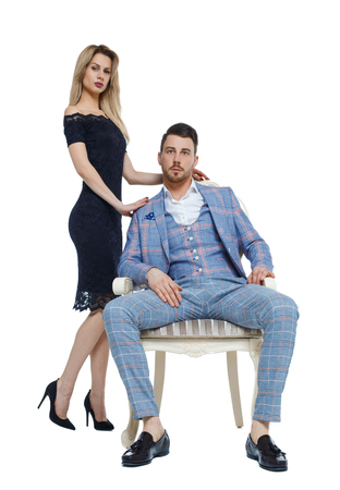 Front view of a luxury couple. A man is sitting on an expensive chair, a woman in a dress is standing next to him. Isolated on white background.
