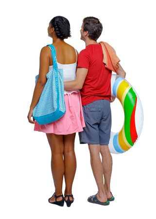Back view of a an international couple with an inflatable circle and beach accessories. beautiful friendly girl and guy together. Rear view people collection. backside view of person.  Isolated over white background. Multi-ethnic couple walking on the beach, standing hugging.