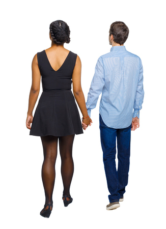 Back view of interracial going couple. walking friendly girl and guy holding hands. Rear view people collection. backside view of person. Isolated over white background. Multi-ethnic couple holding hands goes into the distance.