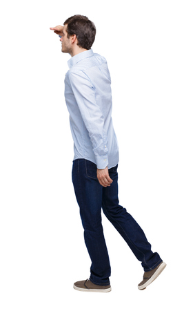 Side view of going  handsome man. walking young guy . Rear view people collection.  backside view of person.  Isolated over white background. The guy in the white shirt walks past putting his hand to his eyes. Imagens