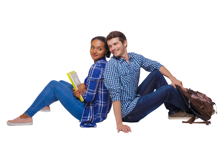 Side view of a couple of students who are sitting on the floor with their backs. Isolated over white background. Students sitting on the floor look at each other and smile. Imagens