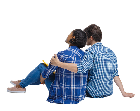 Back view of a multiethnic young couple sitting on the ground and hugging. Rear view people collection.  backside view of person.  Isolated over white background. Young couple looks to the sky, embracing and sitting on the ground.