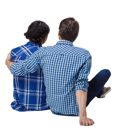 Back view of a multiethnic young couple sitting on the ground and hugging. Rear view people collection. backside view of person. Isolated over white background. The guy hugs his girlfriend by the shoulders.
