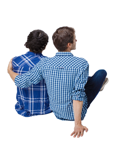 Back view of a multiethnic young couple sitting on the ground and hugging. Rear view people collection. backside view of person. Isolated over white background. A guy and a girl at a picnic.