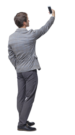 Back view of businessman in a suit making a selfie. rear view people collection. Isolated over white background. backside view of person. Businessman shoots on outstretched hand.