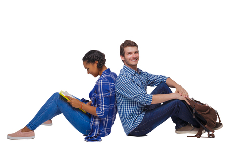 Side view of a couple of students who are sitting on the floor with their backs. Isolated over white background. Students with their backs pressed to sit on the floor.