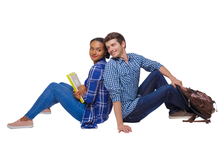 Side view of a couple of students who are sitting on the floor with their backs. Isolated over white background. Students are flirting sitting on the floor.