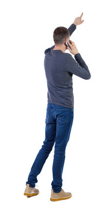 Back view of  pointing young men talking on cell phone. Young guy  gesture. Rear view people collection.  backside view of person.  Isolated over white background. A man in a gray jacket talking on a smartphone and pointing to the top. Imagens