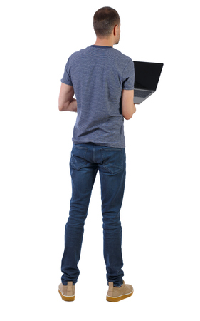 Back view of a man who is standing with a laptop. Rear view people collection.  backside view of person.  Isolated over white background. A young professional checks the information in a laptop. Imagens