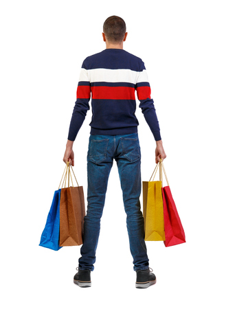 back view of man  with shopping bags . beautiful brunette guy in motion.  backside view of person.  Rear view people collection. Isolated over white background. A guy in a striped sweater stands with multi-colored packages. Imagens