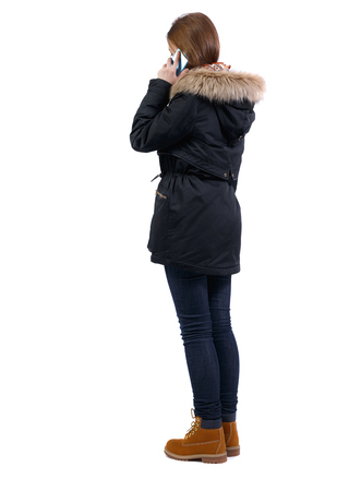 back view of woman in winter jacket talking on mobile phone. rear view people collection. Isolated over white background. backside view of person. A girl in a black park stands with a phone attached to her ear.