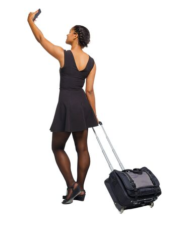 Back view of a black African-American with a suitcase with smartphone. backside view of person. Rear view people collection. Isolated over white background. Reklamní fotografie